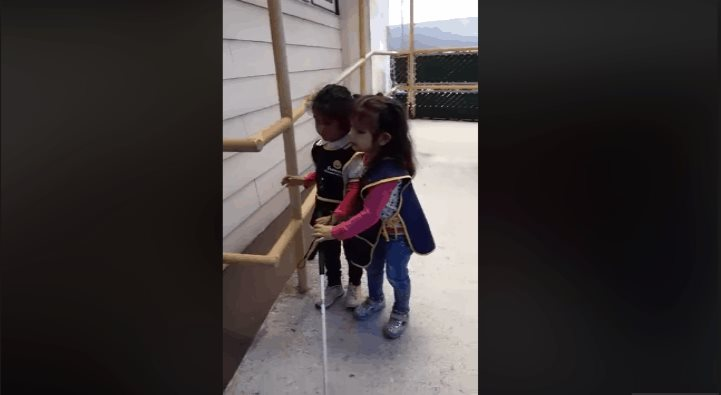 Niña invidente enseña a su compañera a usar el bastón guía