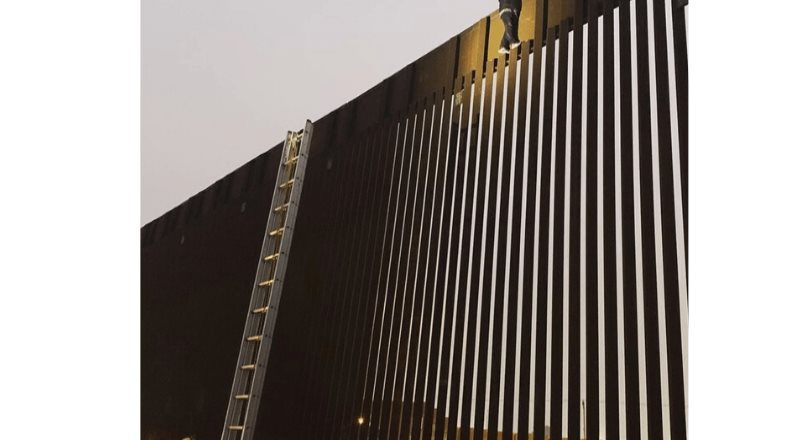 Patrulla Fronteriza y Bomberos de Tijuana auxilian a hombre bajar del muro fronterizo